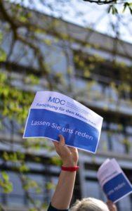 """Mitarbeiter des MDC hält einen Zettel mit der Aufschrift """"Lassen Sie uns reden"""" hoch."""
